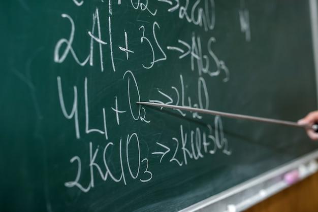 Main de l'enseignant tenant le pointeur et montrant des formules dans la leçon de chimie sur le tableau noir. éducation hors ligne
