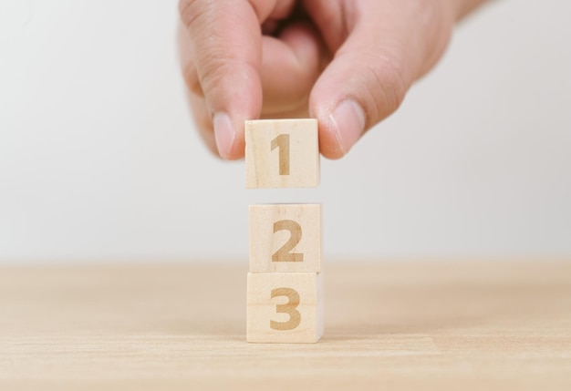 Main d'entreprise organisant l'empilement de cubes de bois comme escalier. processus de réussite de croissance de concept d'entreprise sur fond blanc, espace de copie.