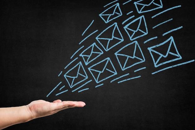 Main Avec Des Enveloppes De Papier Tiré Dessus Photo gratuit