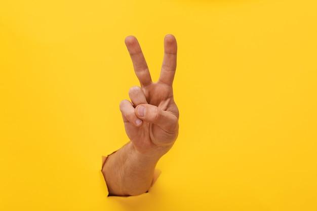 Main sur l'espace de copie papier déchiré couleur tendance jaune