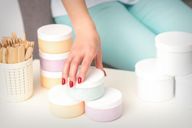 La main d'esthéticiennes prend le pot avec des cosmétiques de la table offrant et vendant des produits cosmétiques crème hydratante pâte de cire