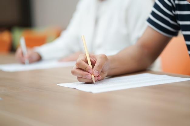 Main d'étudiant à l'aide d'un crayon pour faire l'examen de texte