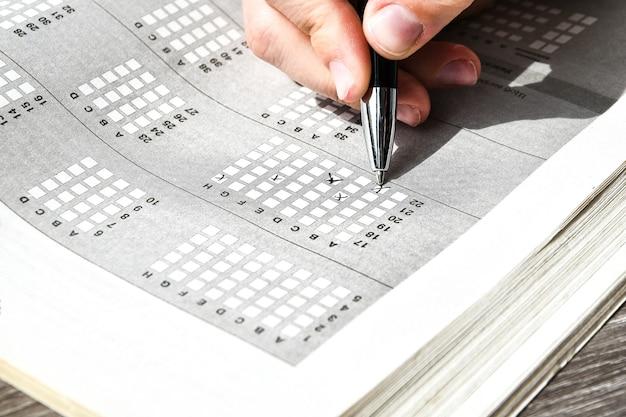 Main de l'étudiant avec un crayon pour l'examen