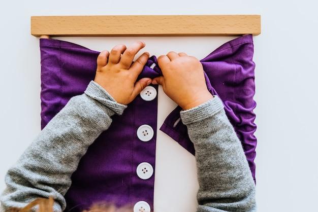 Main d'un étudiant manipulant du matériel montessori à l'intérieur d'une salle de classe.