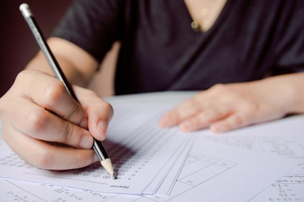 Main d'étudiant tenant un crayon écrivant un choix choisi sur des feuilles de réponses et des feuilles de questions de mathématiques