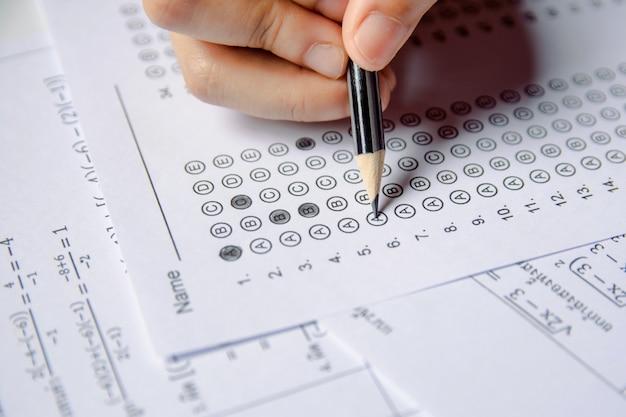 Main d'étudiant tenant un crayon écrivant un choix choisi sur des feuilles de réponses et des feuilles de questions mathématiques
