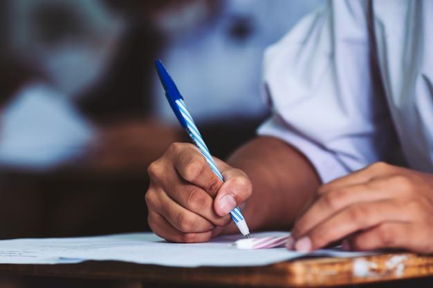 Main d'étudiant tenant un stylo et prenant un examen en classe avec le stress