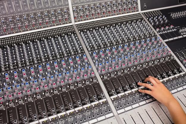 Main d'une étudiante à l'aide d'une table de mixage sonore