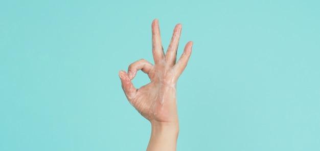 Main faisant un geste de signe de main okey (ok) et laver du savon moussant pour les mains sur fond vert menthe ou bleu tiffany.