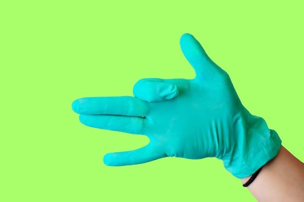 La main femelle dans le gant bleu de latex fait un geste ressemblant à un chien avec la bouche ouverte
