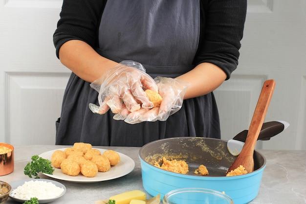Main féminine à l'aide de gants en plastique faisant arancini, arrondissant le riz arancini. cuisiner étape par étape dans la cuisine