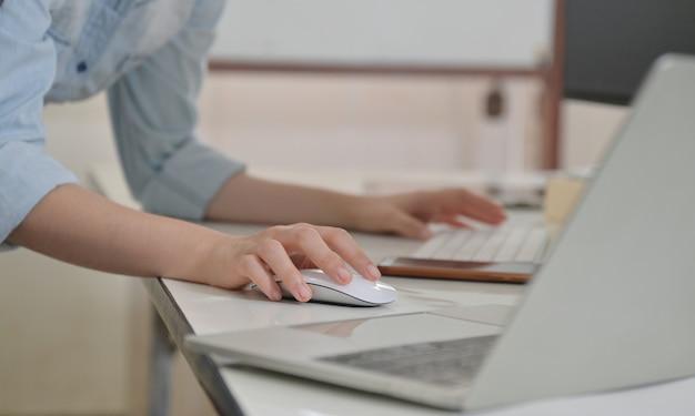 Main féminine à l'aide d'une souris et d'un clavier d'ordinateur.