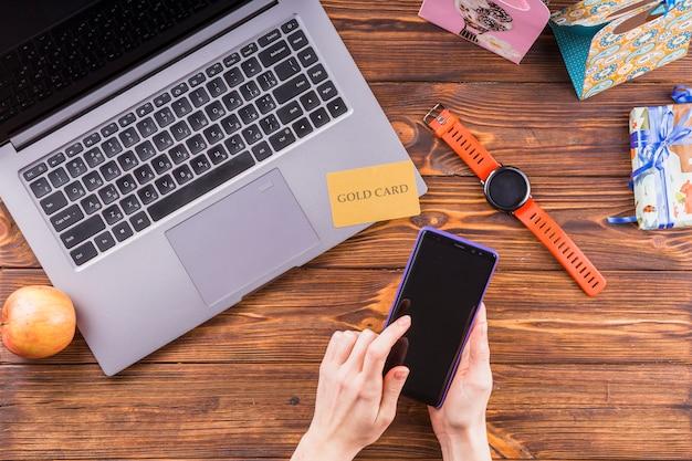 Main féminine à l'aide d'un téléphone portable sur une surface en bois