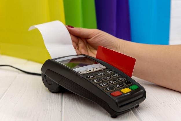 Main féminine en appuyant sur les boutons sur le terminal avec carte