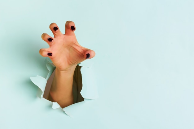 Main féminine, atteindre, par, déchiré, feuille papier bleu