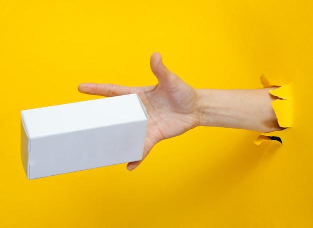 Une main féminine attrape une boîte blanche à travers du papier jaune déchiré. concept créatif minimaliste