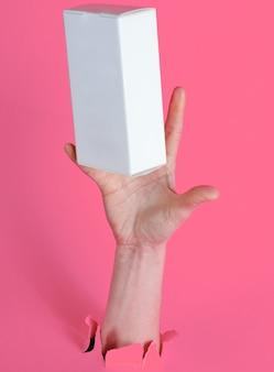 Une main féminine attrape une boîte blanche à travers du papier rose déchiré. concept créatif minimaliste