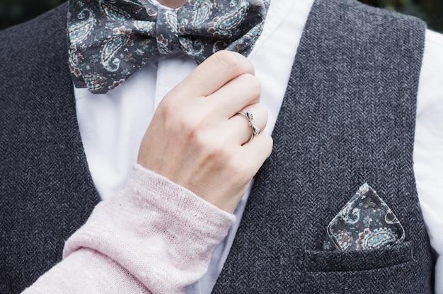 Une main féminine avec une bague en diamant tient doucement un noeud papillon