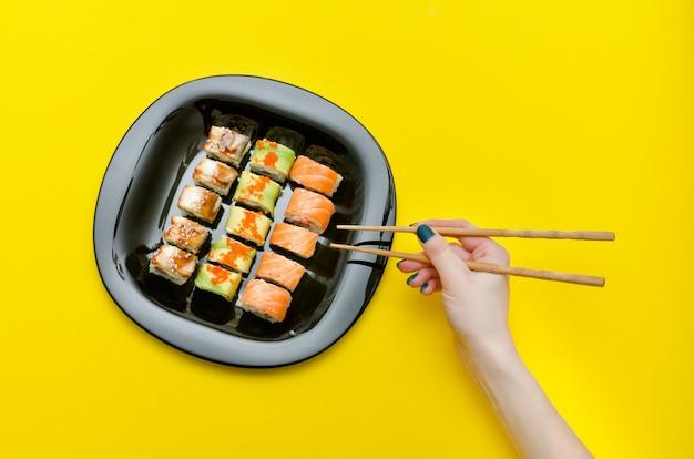 Main féminine avec des baguettes et une assiette avec divers rouleaux de sushi. vue de dessus