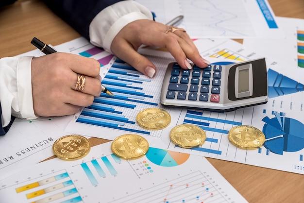 Main féminine avec bitcoin et graphique d'entreprise