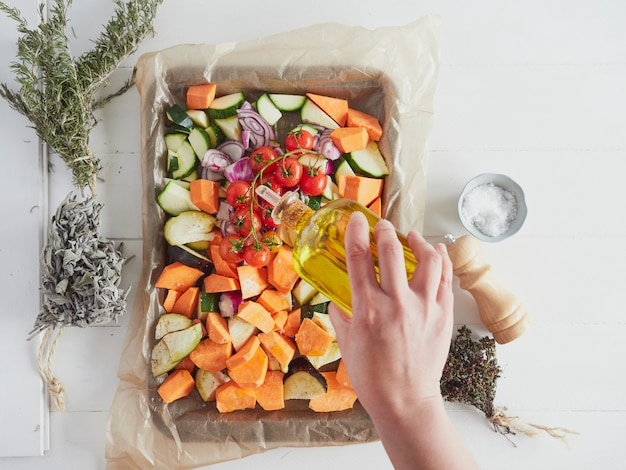 Main féminine avec une bouteille d'huile d'olive assaisonnement de légumes sur une plaque de cuisson
