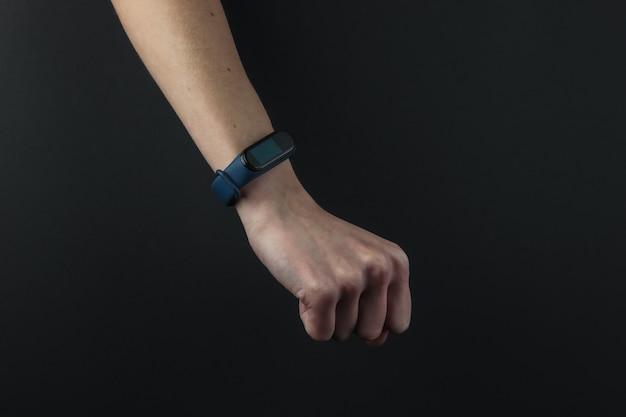 Main féminine avec un bracelet intelligent sur fond noir. gadgets modernes