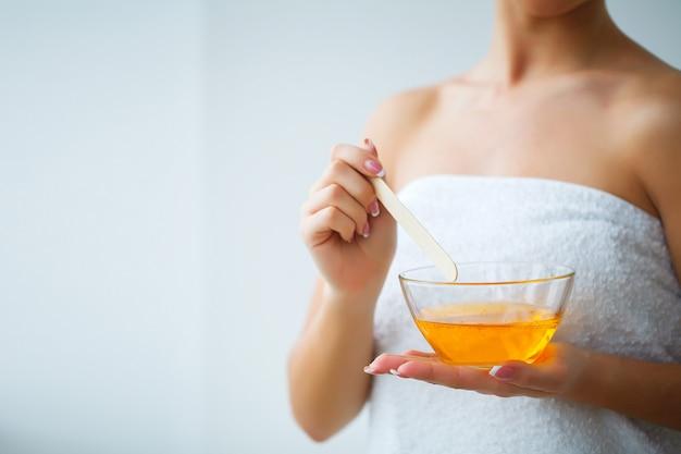 Main féminine et cire de paraffine orange dans un bol.