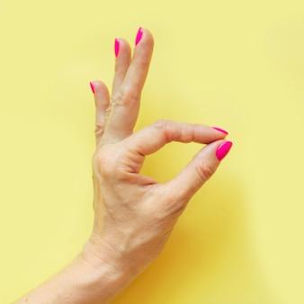 Main féminine avec un clou rose sur jaune ..