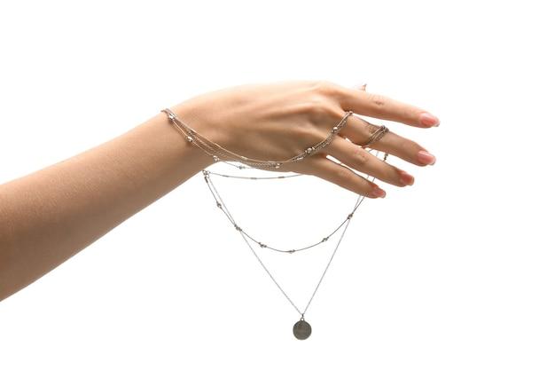 Main féminine avec collier élégant sur fond blanc