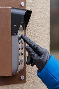 Une main féminine compose le code sur l'interphone. fermer.