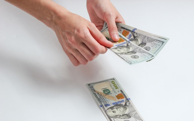 Main féminine comptant des billets de cent dollars sur blanc.