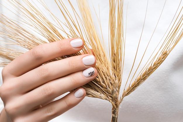 Main féminine avec la conception des ongles blancs, gros plan.