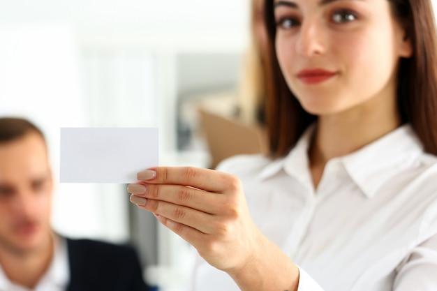 Une main féminine en costume donne une carte de visite vierge au visiteur