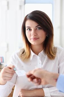 La main féminine en costume donne une carte de visite vierge à une femme