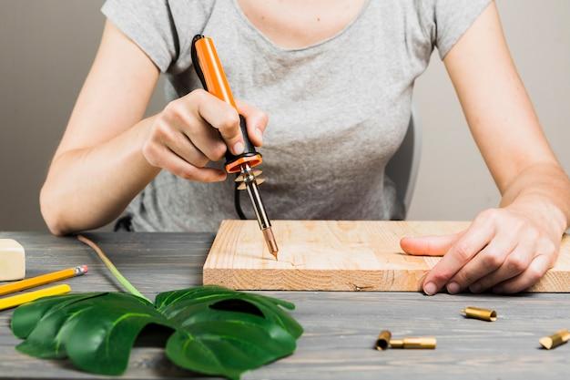 Main féminine coupant la forme de bois dur à l'aide d'une machine à souder près de la feuille de monstera sur une table