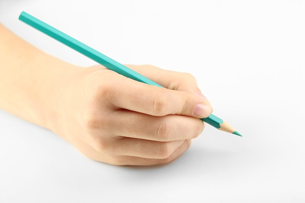 Main féminine avec un crayon coloré isolé sur blanc