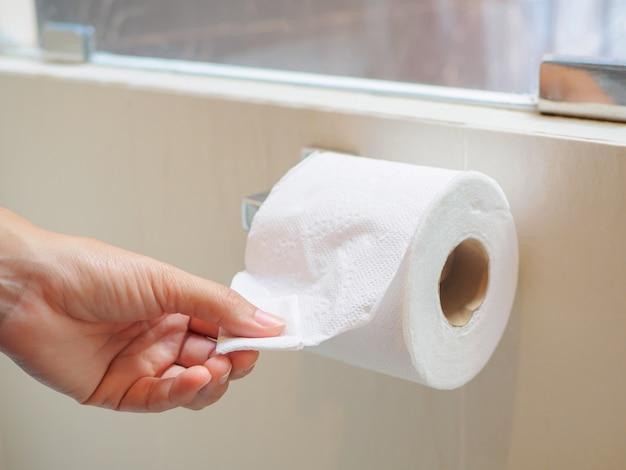 Une main féminine cueillant un tissu blanc d'un rouleau de tissu dans les toilettes.