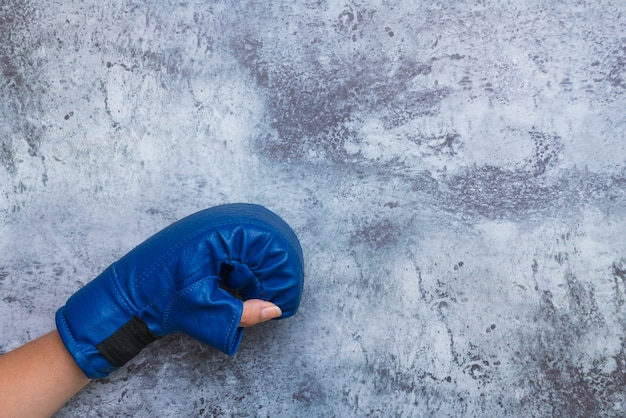 Main féminine dans le gant de formation bleu sur fond de mur en béton gris.