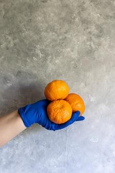 Une main féminine dans un gant jetable bleu contient différents objets. vaporisez pour la désinfection, la mandarine et un tas de verts sur une table grise.