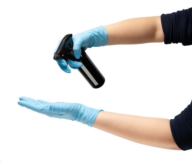 Main féminine dans un gant médical en caoutchouc de protection de couleur bleue, tient une bouteille en métal noir d'un distributeur antiseptique, pour lutter contre les bactéries.