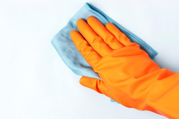 Main féminine dans le gant orange lingettes surface avec un chiffon, fond blanc