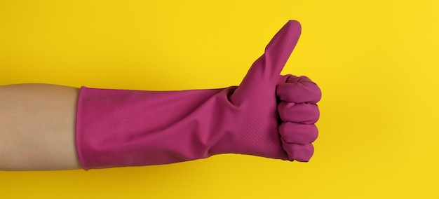 Main féminine dans le gant de travaux ménagers sur jaune