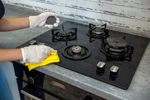 Main féminine dans des gants blancs, nettoyage avec une cuisinière à gaz en mousse avec une surface en verre. travaux ménagers