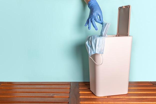 Main féminine dans des gants en caoutchouc jetables jette un masque facial dans la poubelle