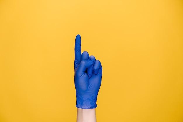 Main féminine dans des gants médicaux montrant aucun