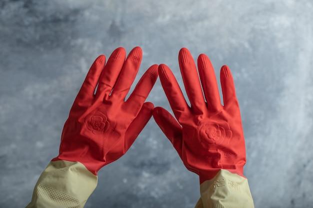 Main féminine dans des gants de protection rouges sur marbre.