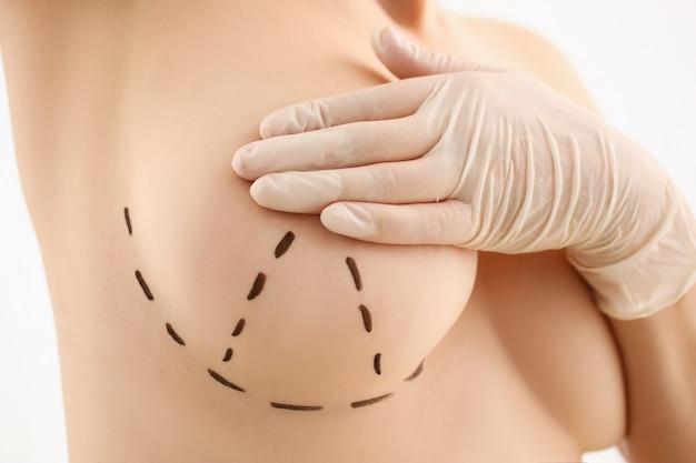 Main féminine dans des gants tenant gros plan du sein