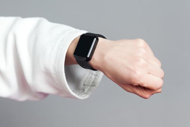 Une main féminine dans une manche blanche avec une montre intelligente montre un moniteur de fréquence cardiaque. concept de soins de santé et de technologie pour le sport professionnel. studio intérieur tourné isolé sur fond gris.