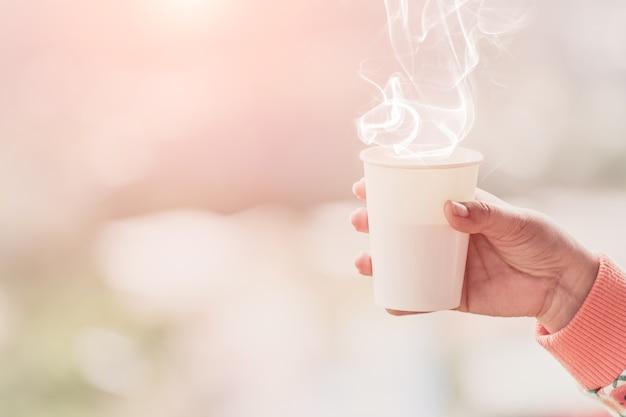 Main féminine dans des mitaines tenant une tasse de thé ou de café chaud.