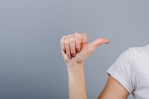 Main féminine dans le poing montrant un doigt isolé sur gris